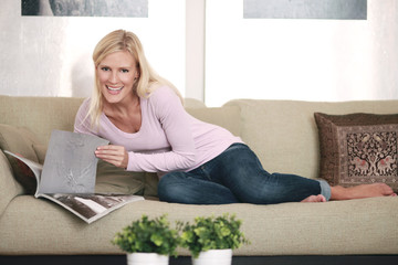 Frau auf Sofa mit Zeitung
