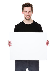 Happy young man showing and displaying placard