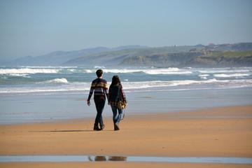 pareja caminando por la playa de oyambre, cantabria