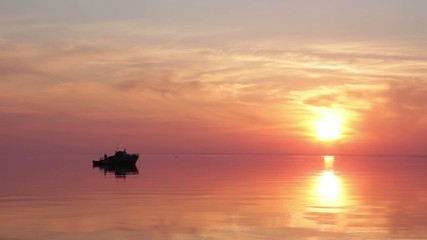 video of a floating boat at sunset