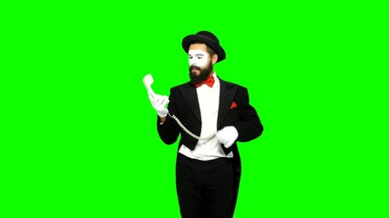 Funny man mime hears the ring of telephone and answers on green