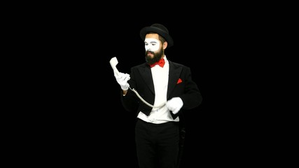 Funny man mime hears the ring of telephone and answers, alpha
