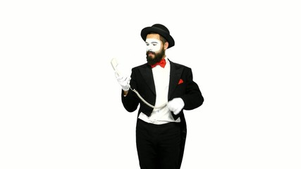 Funny man mime hears the ring of telephone and answers on white