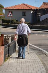 anciano caminando por las calles de comillas