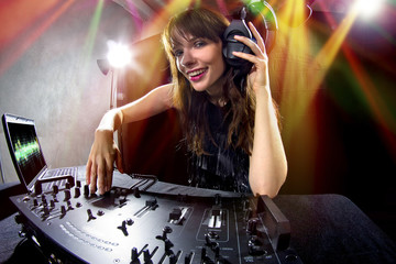 caucasian female dj using a mixer and computer to play mp3s