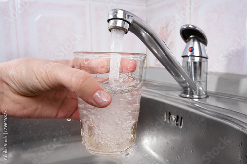 hand pours water into a glass from  faucet - 79645875