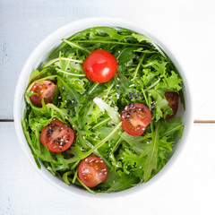 Mixed salad with arugula, cherry tomatoes and sesame seeds.