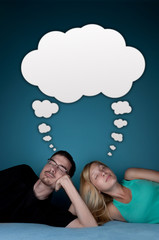 Couple on the bead dreaming with cartoon cloud over head