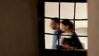 People Passing Iron Window