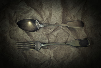 Antique silver cutlery - fork and false on vintage background