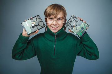 European-looking boy of ten years in glasses holding a hard driv