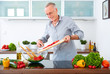 Mature man in the kitchen prepare salad IX - 79649842