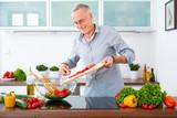 Mature man in the kitchen prepare salad IX
