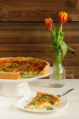 Cheese tart with red wine and red tulips on wooden background