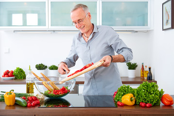 Mature man in the kitchen prepare salad IX