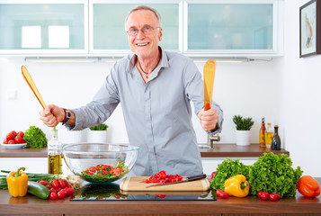 Mature man in the kitchen prepare salad IV