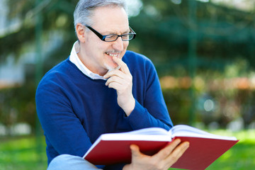 Mature man reading a book outdoor