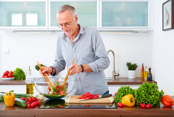 Mature man in the kitchen prepare salad V