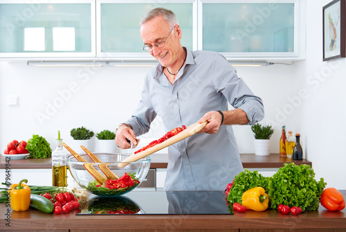 Mature man in the kitchen prepare salad IX - 79649842