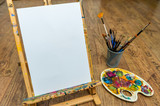 easel palette and brushes with empty white canvas - 79652236