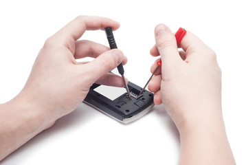 Close-up Of Human Hand Repairing Cellphone With Screwdriver