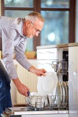 Senior man empty out the full dishwasher