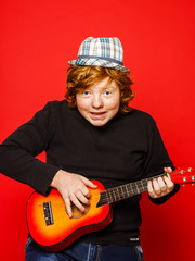 Red-hair funny teenage boy playing little guitar