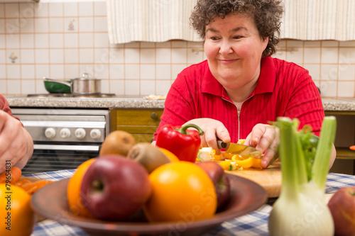 Geistig behinderte Frau schneidet Paprika am Tisch - 79654831