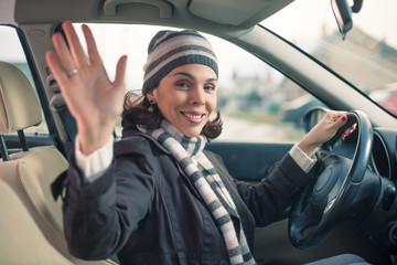 Happy young woman driving a car and waving