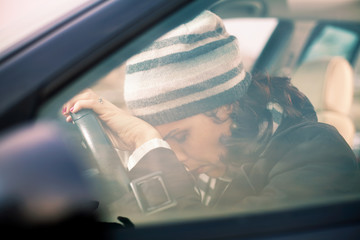 Tired woman leaning her head on the steering wheel
