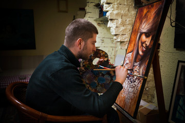 Young painter working on oil painting portrait