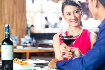 Asian couple with wine in Restaurant