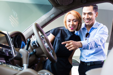 Asian couple choosing luxury car in dealership