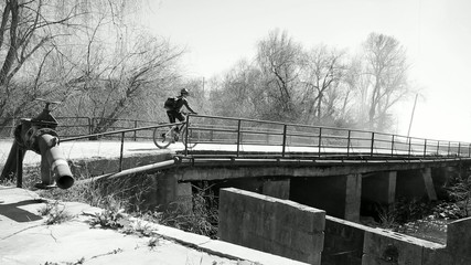 monochrome mountain bicycle riding on a bridge in a foggy day