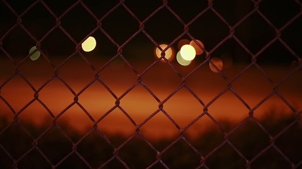 View from behind a fence of Cars driving by in the evening