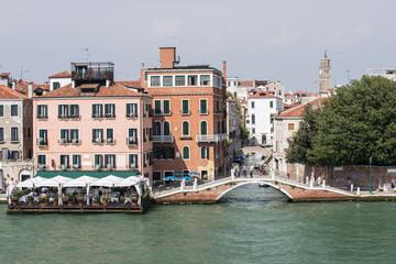 Quay, restaurant and bridge over channel in Venice