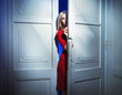 Blond woman carefully opening the door