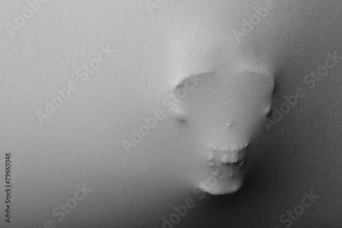 Skull pressing through fabric as horror background - 79663048