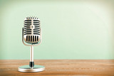 Fototapety Retro microphone on wooden table on blue background