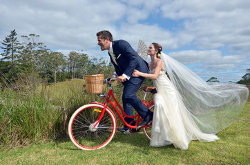 Husband and wife ride on bicycle on their wedding Day