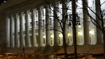 Panning across the columns of a US Courthouse at night