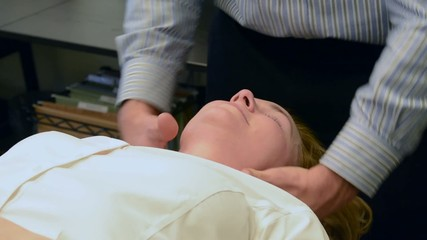 A woman receiving a neck adjustment in a chiropractic office
