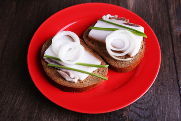 Sandwiches with lard and onion on plate on wooden background