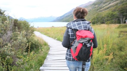 Woman with backpack walking towards Argentino Lake