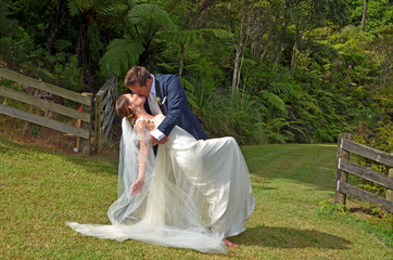 Husband and wife kiss on their wedding Day outdoors