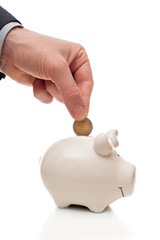 male hand putting a coin into piggy Bank