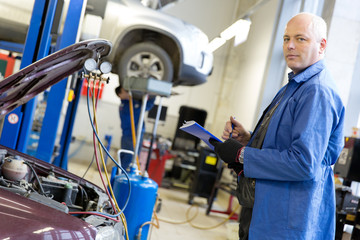 Mechanic with notebook during car conditioner refilling