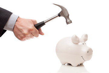male hand with a hammer and a piggy Bank