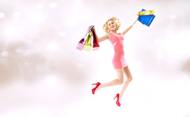 Delighted jumping lady with shopping bags