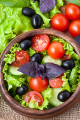 Superfood vegetarian salad with tomato and olives on rustic